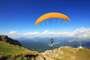 yellow paraglider against blue sky with hills and clouds