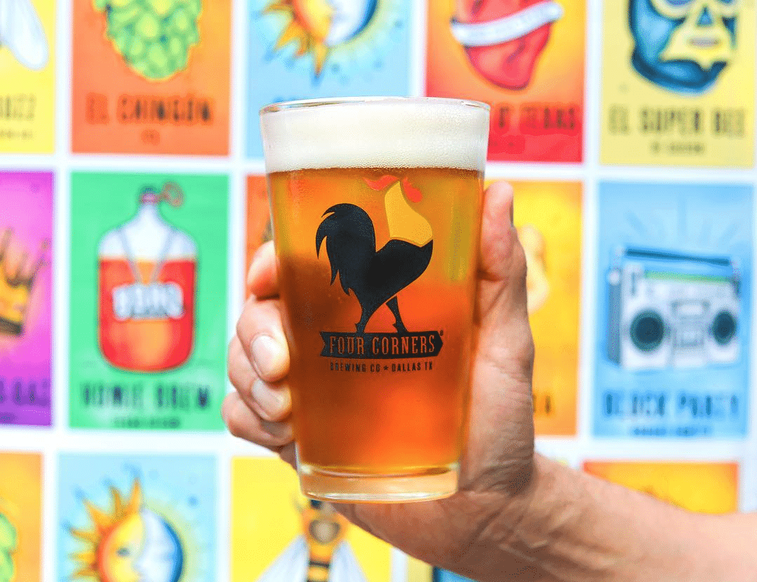 hand holding a glass of beer in front of a colorful wall