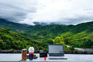 A laptop and camera sit on a ledge in front of rolling green mountains