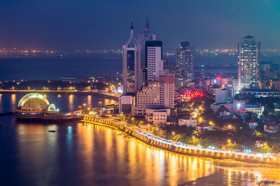 Escena nocturna de la bahía de Qingdao con los rascacielos principales del distrito occidental de la ciudad y la playa de Zhanqiao iluminada, Qingdao, provincia de Shandong, China, Asia.