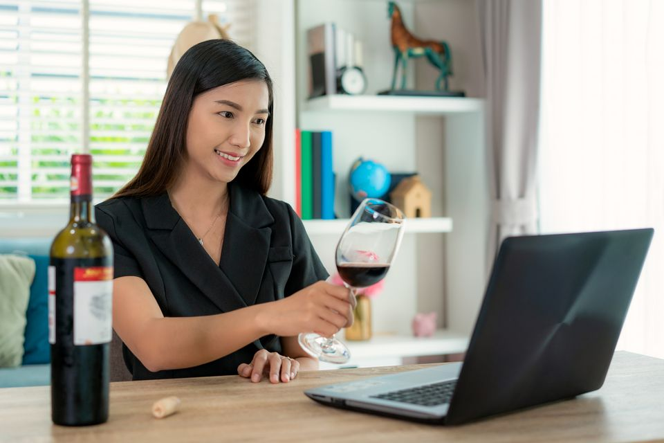a woman drinking wine and toasting with friends on a video chat