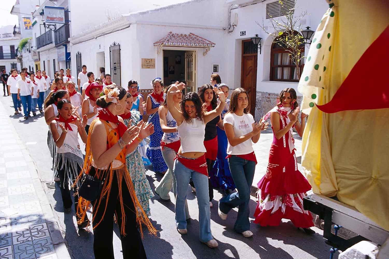 People in a procesion on a sunlit street, Romeria de San Isidro, Nerja