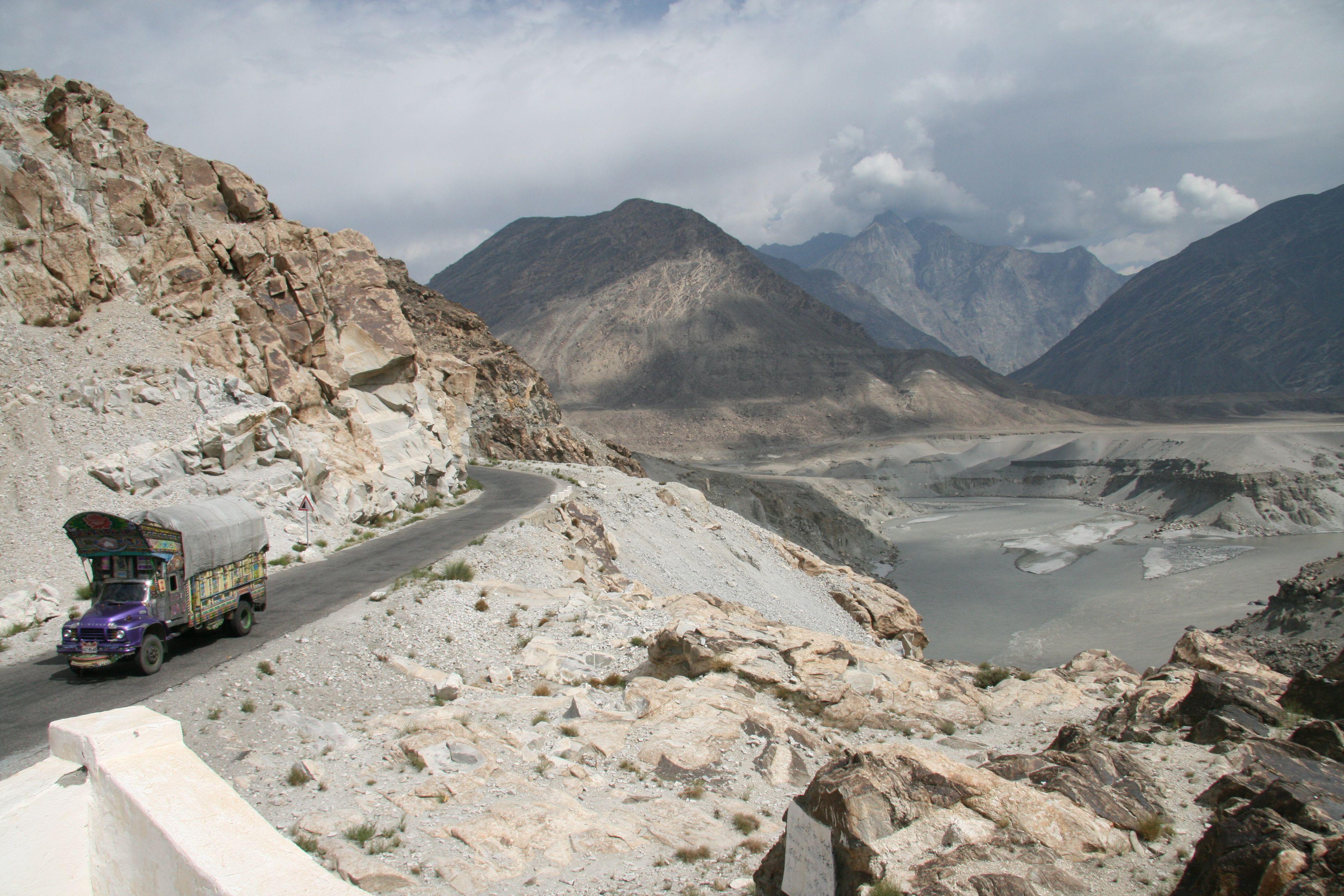 Un camión que circula por la carretera de Karakoram con vistas panorámicas de las montañas al fondo
