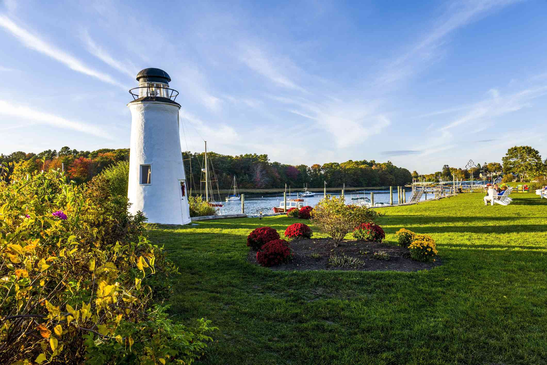 small white lighthouse in a lush green field in maine