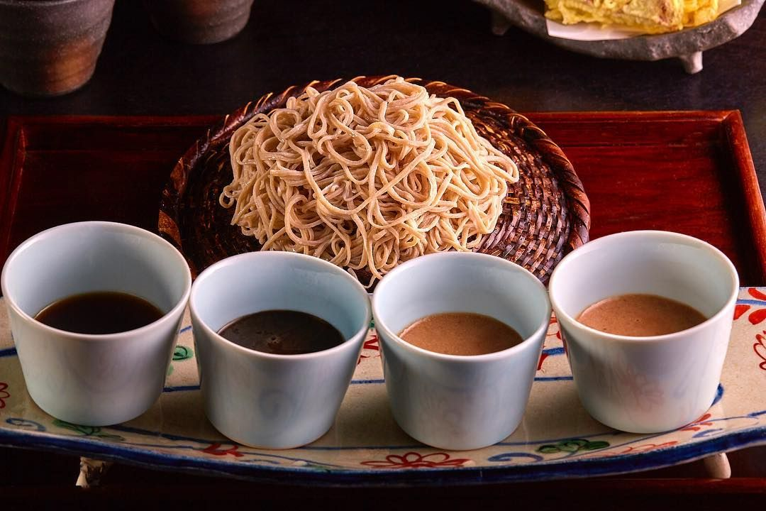 Round, woven plate with a pile of soba noodles on it. There are four, sauce filled bowls in front of the noodles