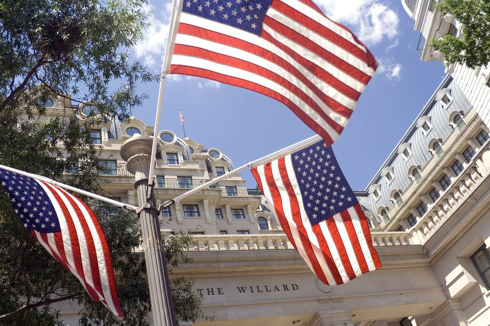 USA, Washington DC, American flags outside The Willard hotel