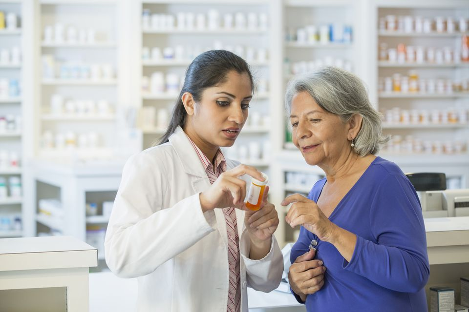 A pharmacist helps a mature customer learn how to take her prescription medication