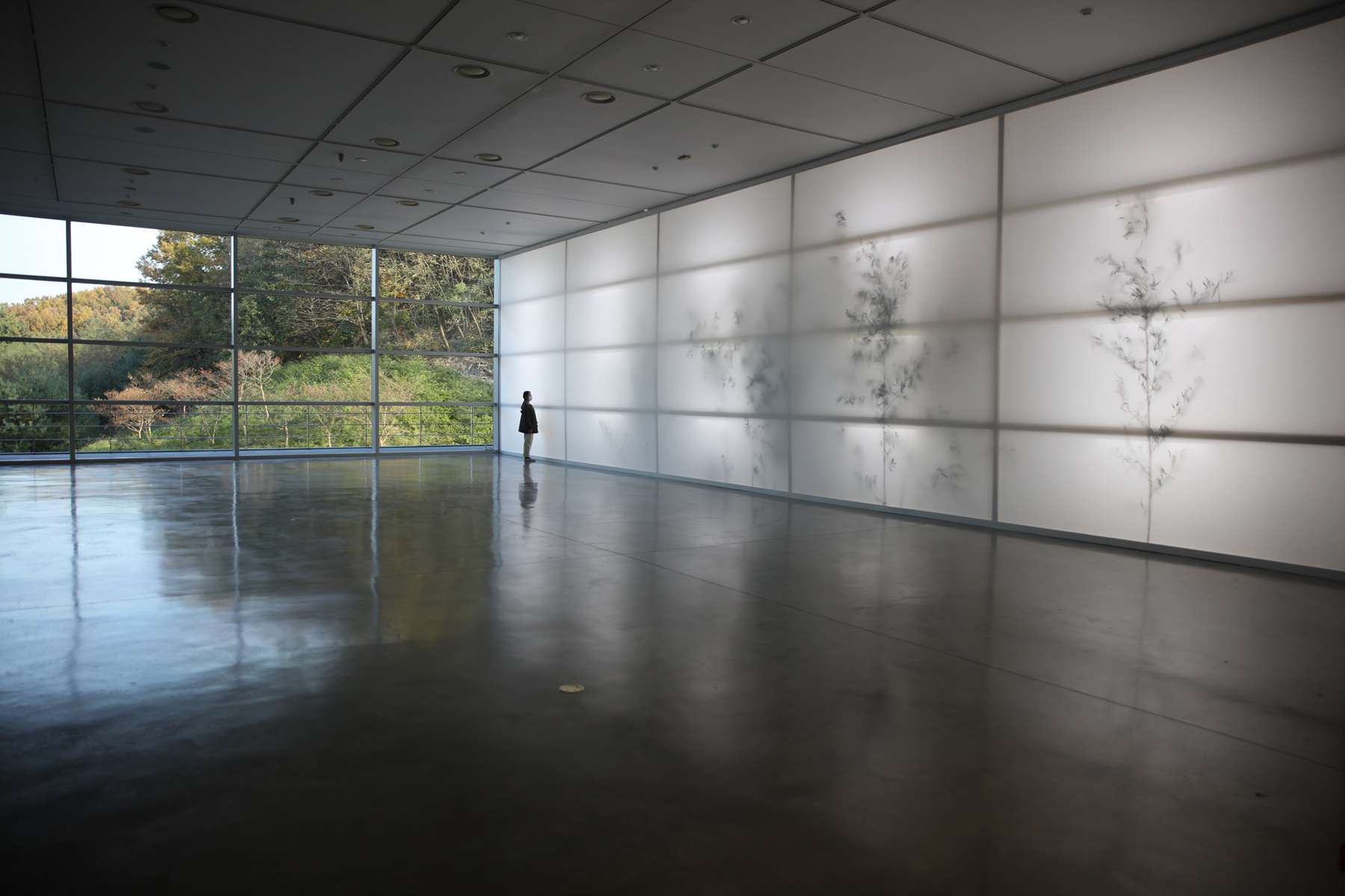 Person in silhouette standing in front of a large art installation