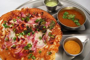 A plate of Indian food with three sauces