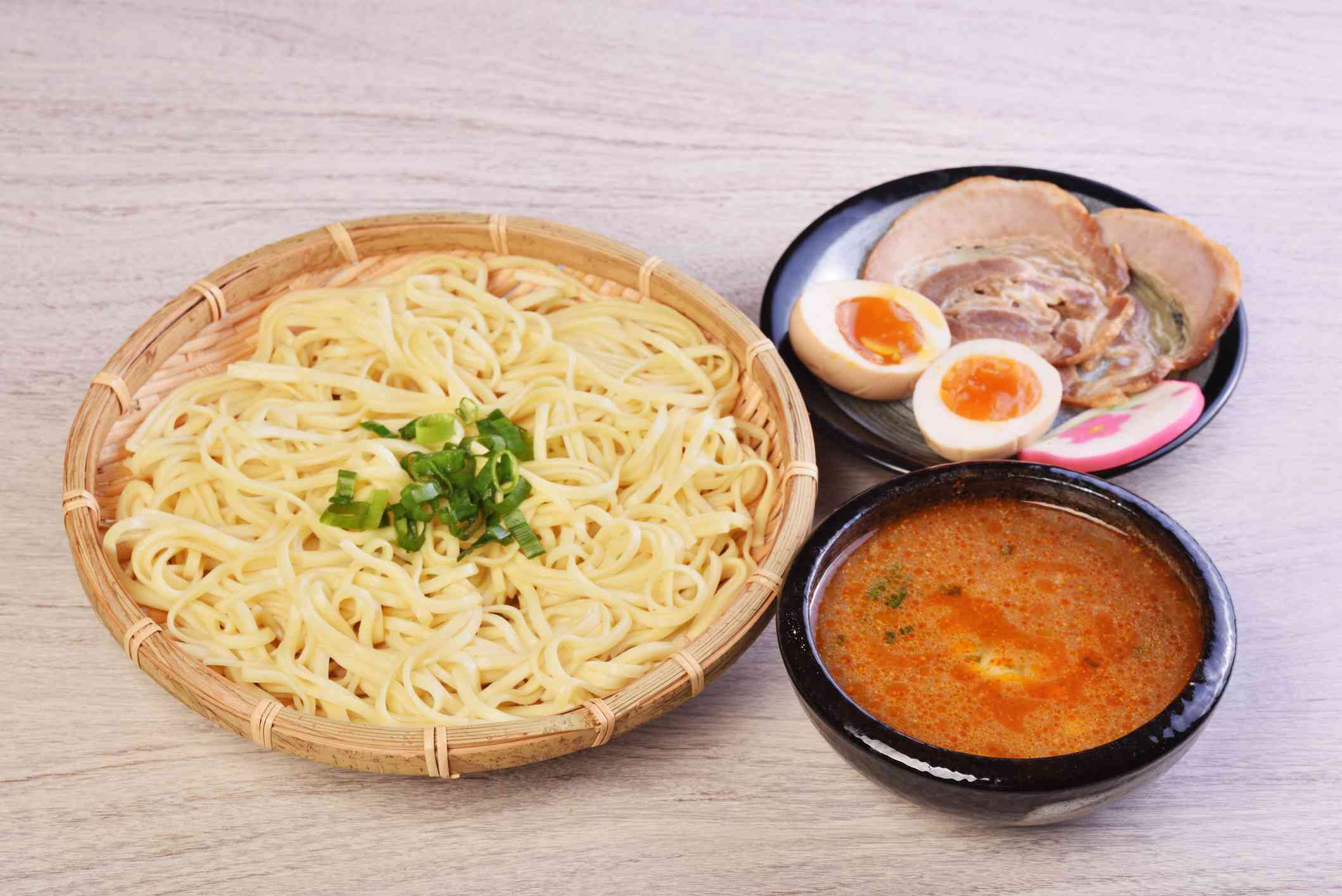 basket of noodles next to a bowl of brpth and plate of chashu pork and soft boiled eggs