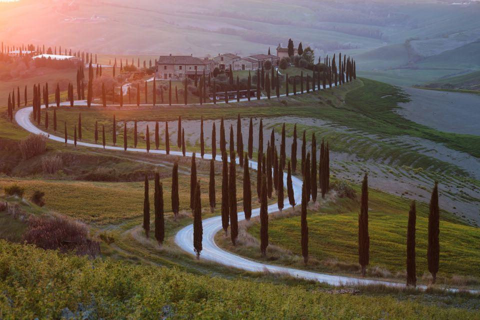 Colorida puesta de sol sobre una granja en la Toscana, Italia