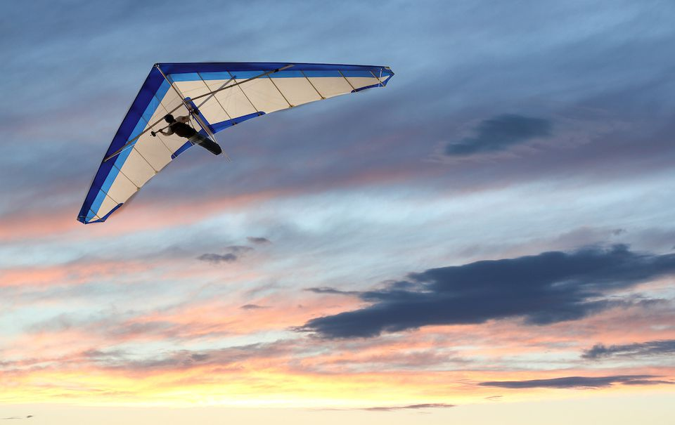 A hang glider in flight with the sun setting