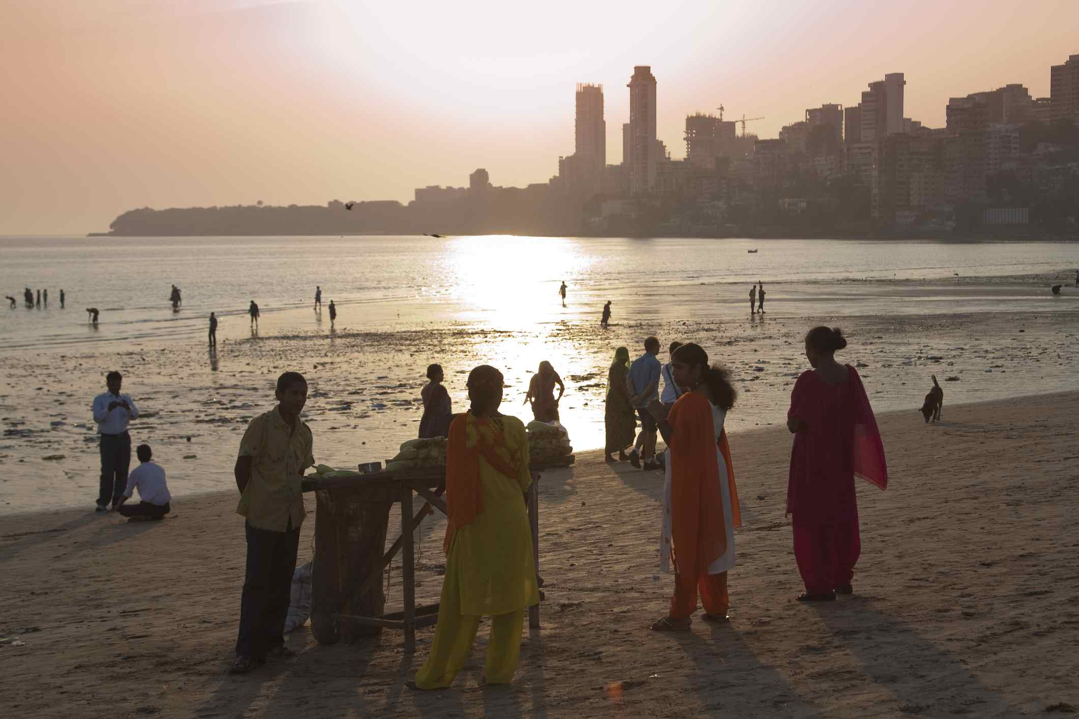 People on Chowpatty beach at sunset with Malabar Hill in background.
