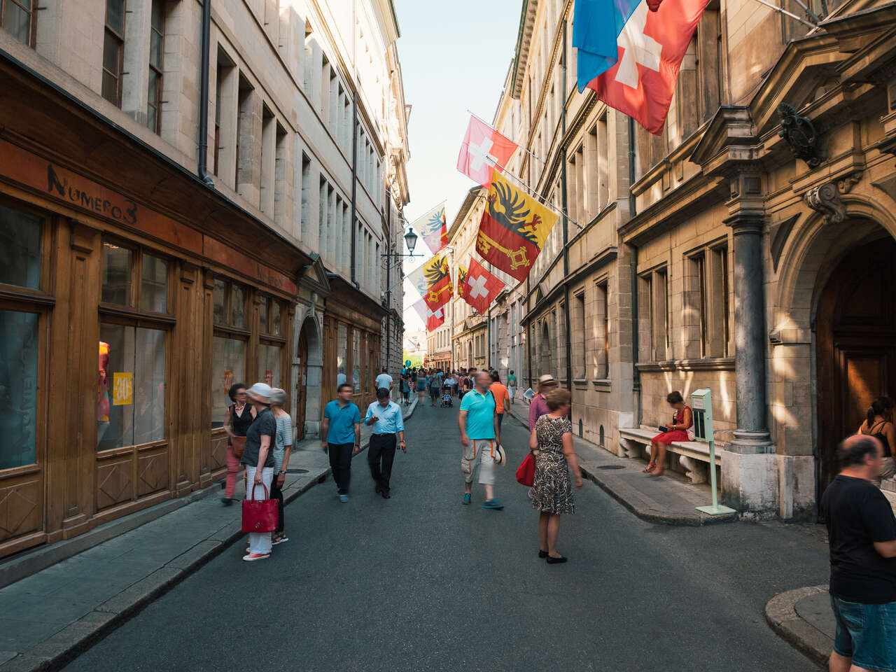 People walking on an Old Town street, with flags attached to buildings