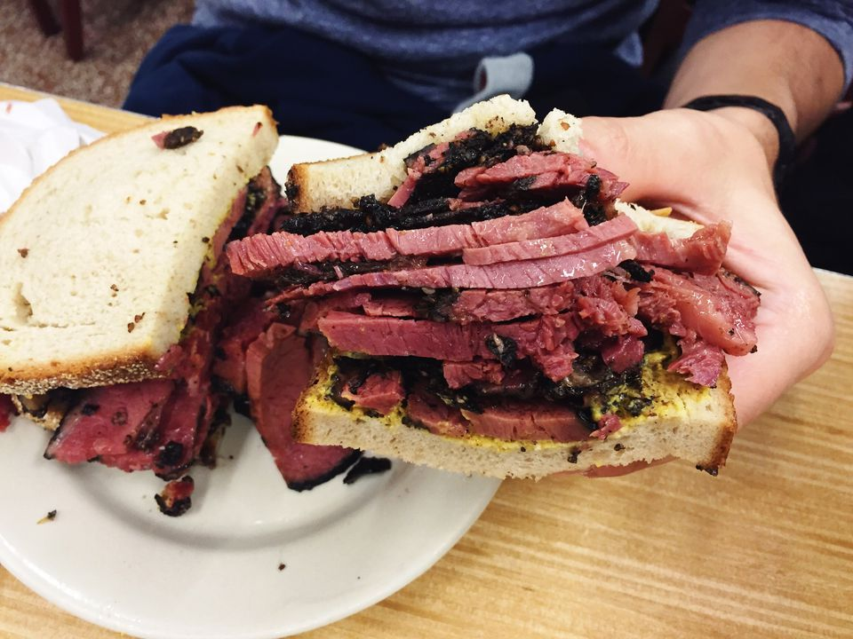 Cropped Image Of Hand Holding Pastrami Sandwich Over Table