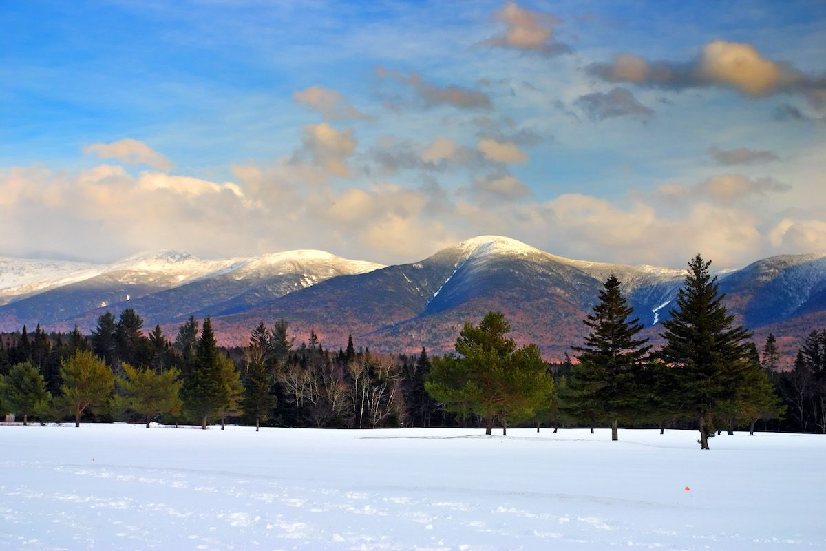Snowcapped mountain peaks rise in the distance behind New Hampshire forests.