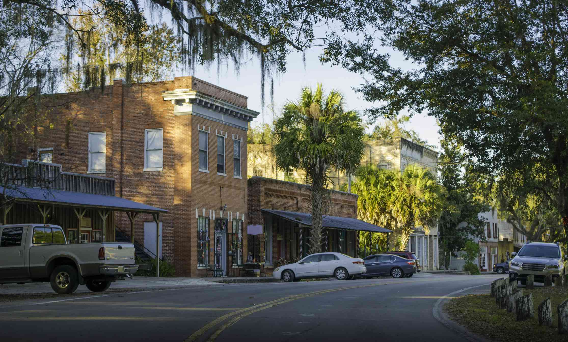 brick buildings on a curving road with a lot of trees in a small florida town