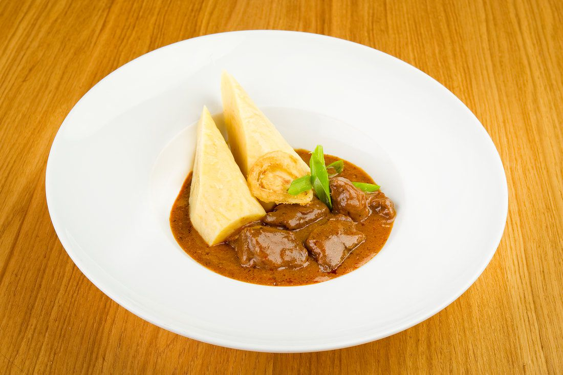 Plate of czech beef goulash in a bowl with a very large edge. There are two bread dumplings in the goulash