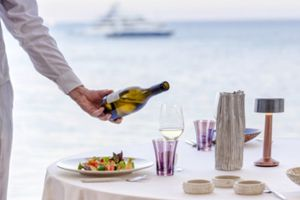 waiter pouring a glass of wine at an outdoor dining table