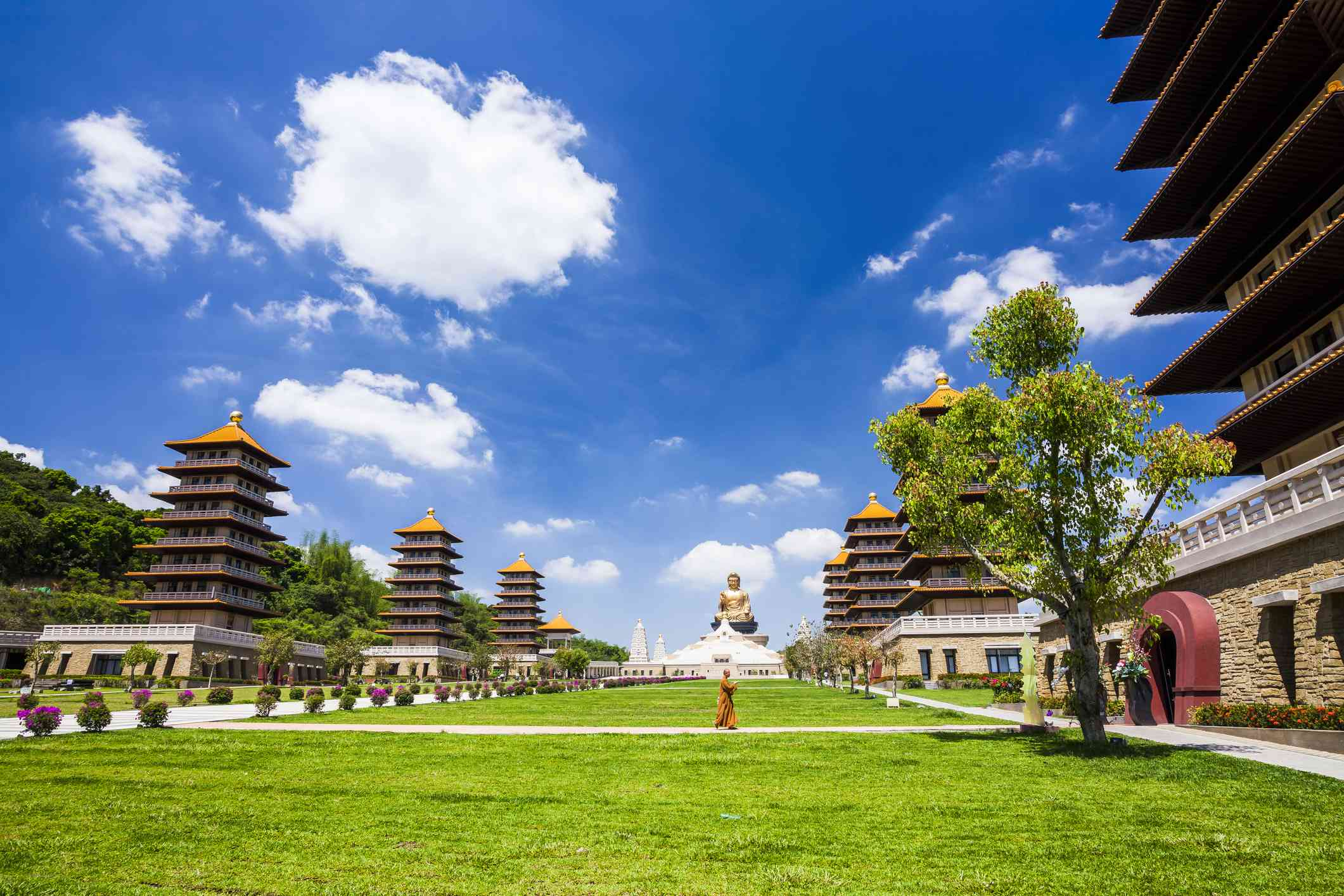 monk in orange robes walking in the Fo Guang Shan Buddha Museum campus with a large buddha statue in the background