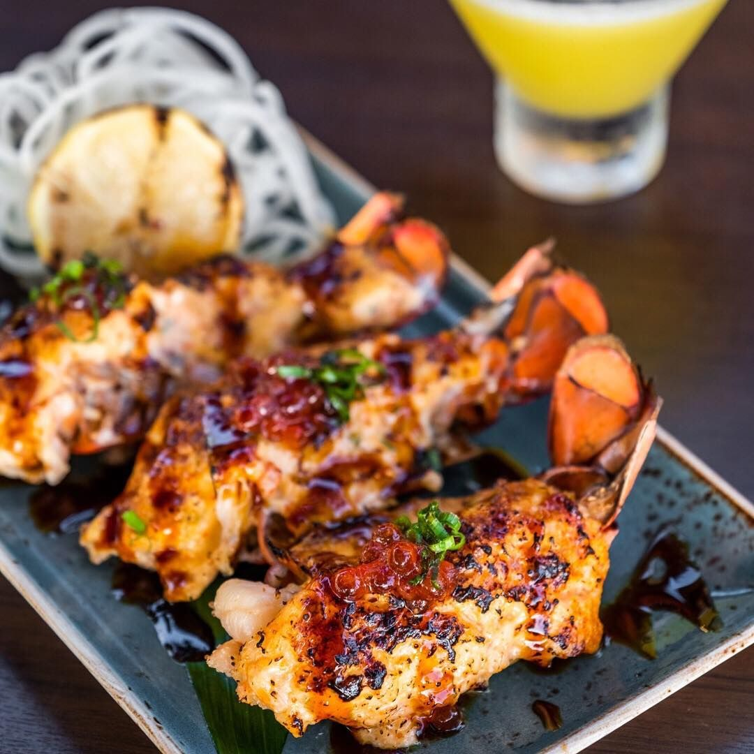 Three lobster tails with fresh crab and kewpie mayo mix broiled and topped with salmon roe, green onion and a sweet unagi glaze drizzled over the top on a plate
