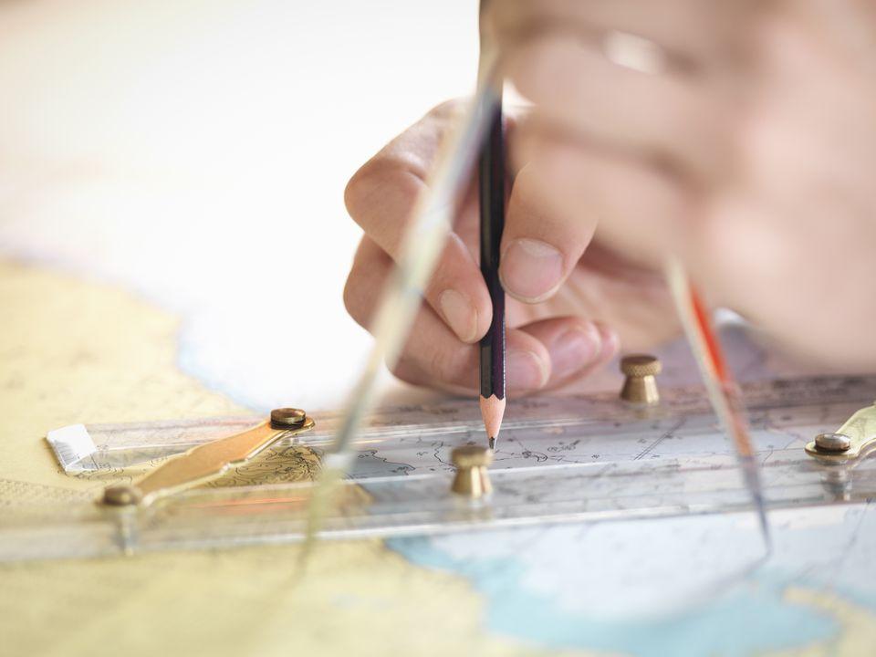 man plotting nautical chart