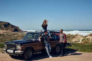 Woman taking photo from roof of car on the coast of Portugal