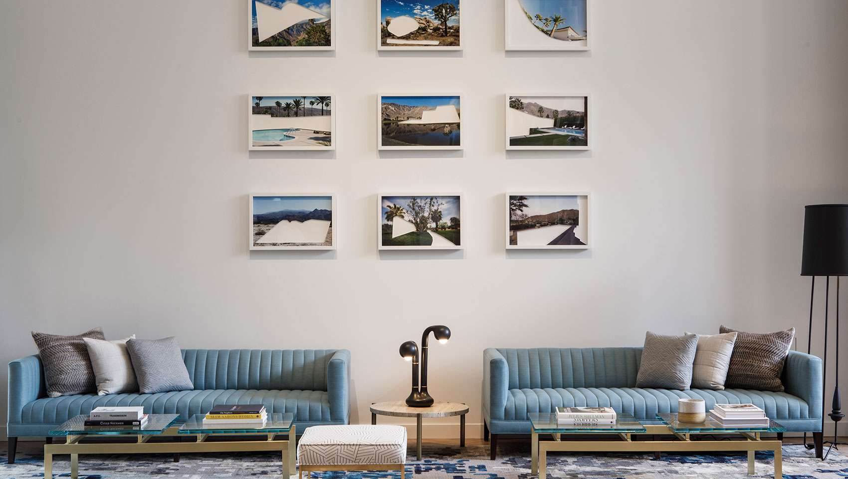 Two blue sofas in a hotel lobby with 9 photographs hanging on the wall above the sofas