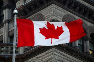 Canadian flag flies in the wind in front of Parliament building