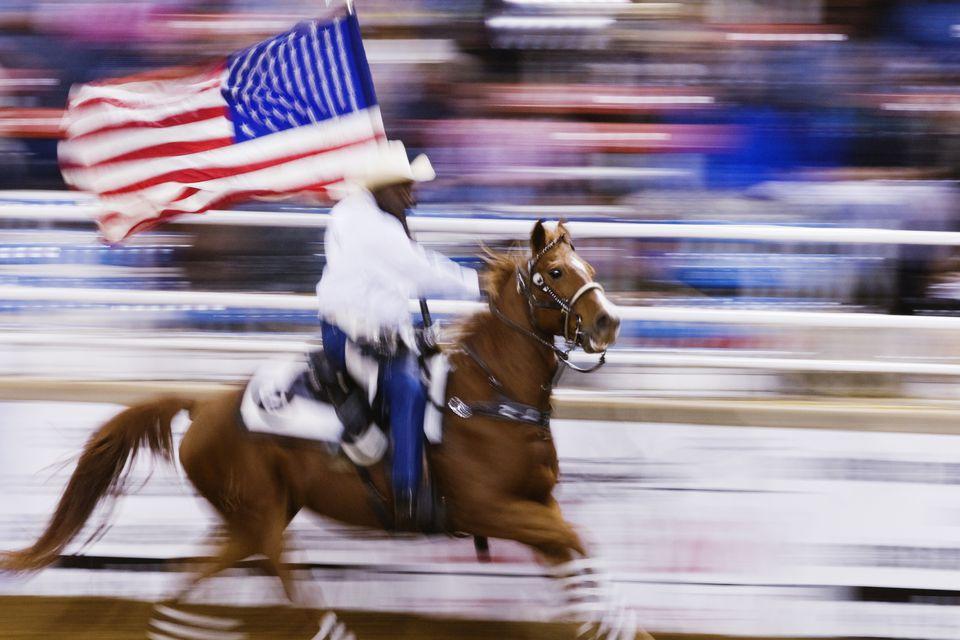 Vista de movimiento borroso de vaquero a caballo con bandera americana en rodeo