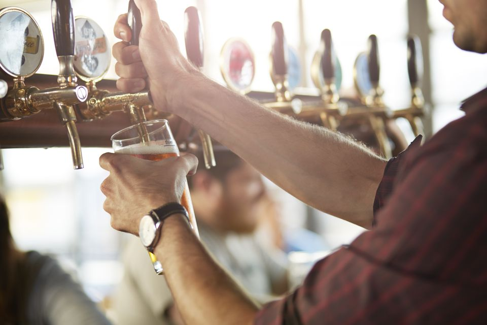 Close-up of bartender pouring cask beers at bar