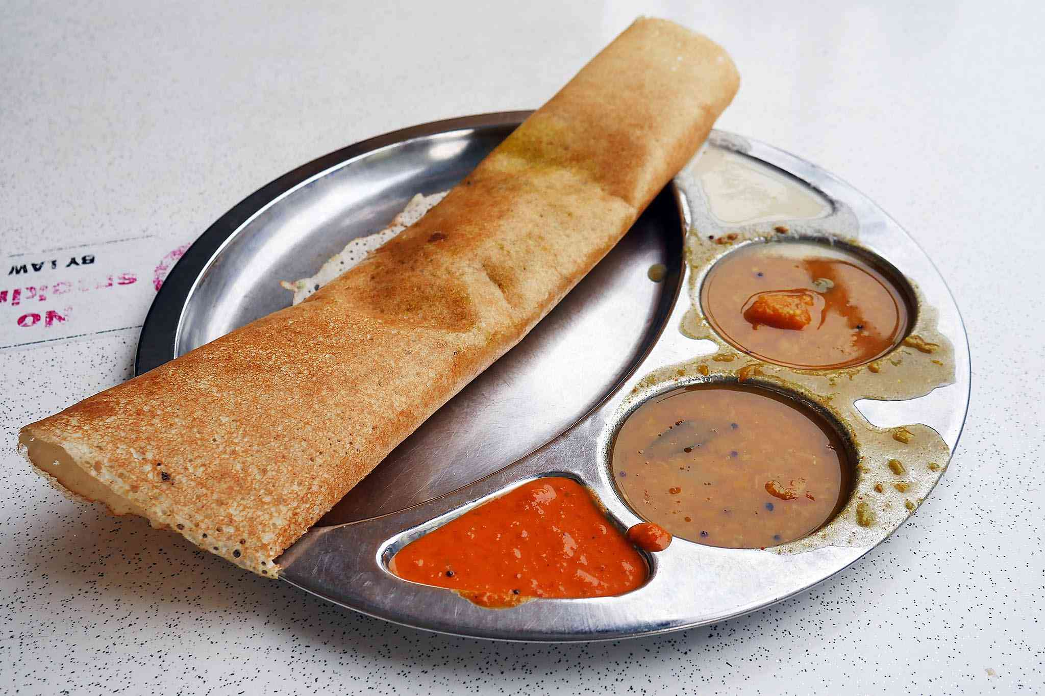 Dosa pancake on plate with side sauces