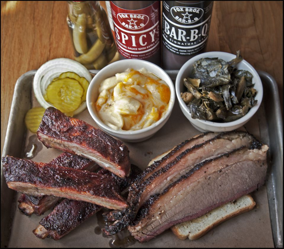 Tray with ribs, sliced brisket, a small cup of collard greens, a small cup of macaroni and cheese, three pickle slices and a slice of onion with a jar of pickled hot peppers and a bottle of spicy and regular barbecue sauce