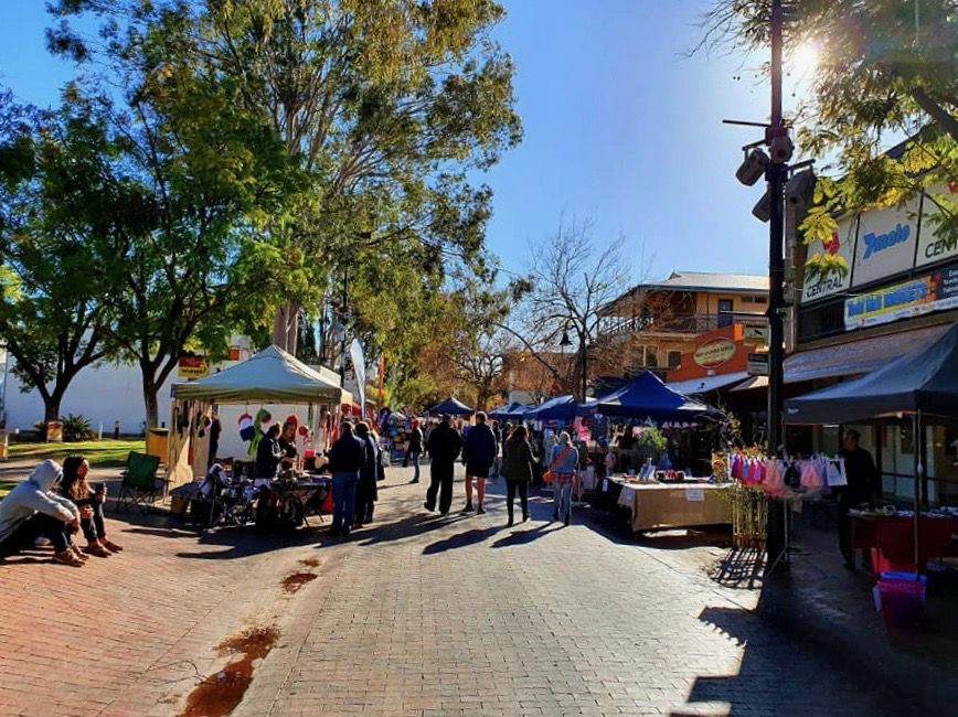 Market stalls with customers on sunny day