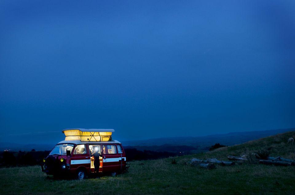 A camper van on a rustic hill at dawn