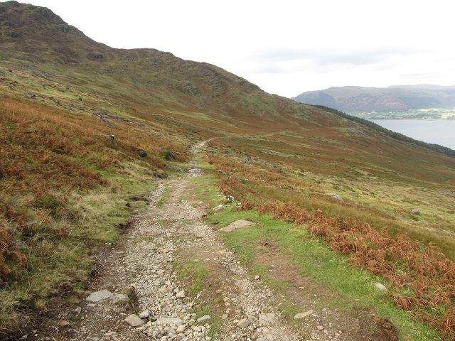 Rocky foot path on the tain trail going along a green and orange hill