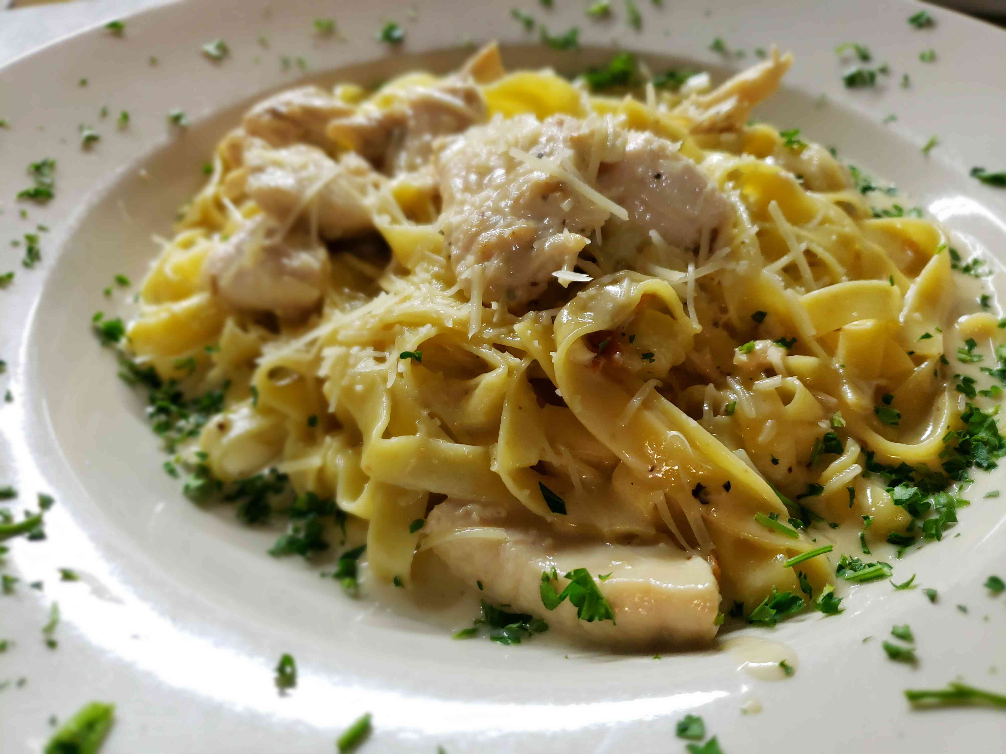 Fettuccine pasta with chicken, shredded parmesan cheese and diced cilantro