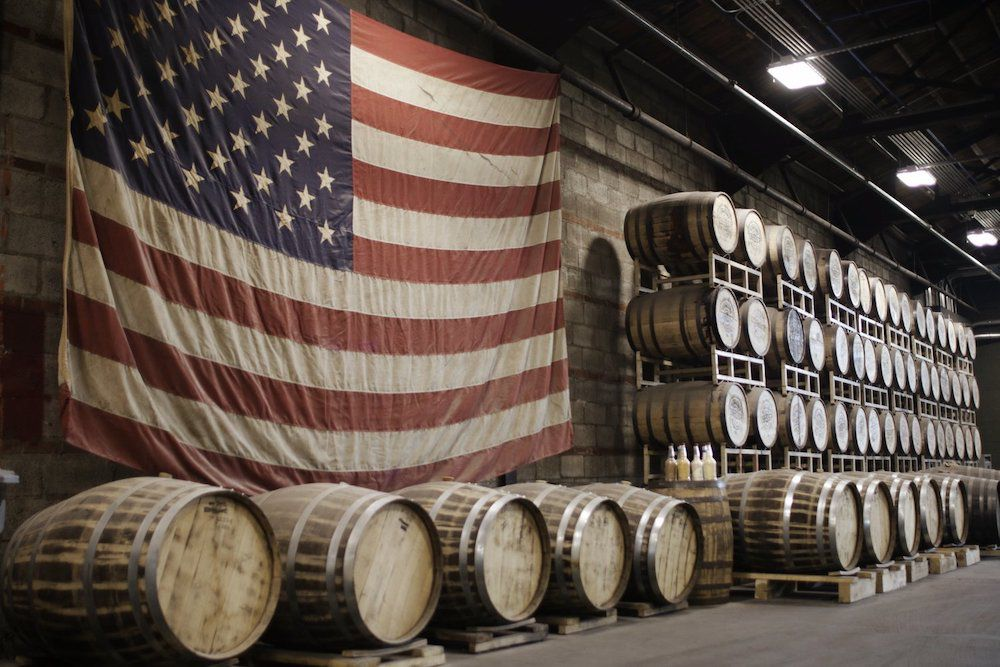 A large, faded american flag with five large whiskey barrels underneathe it and dozens of barrels to the right of the flag at Green Brier Distillery