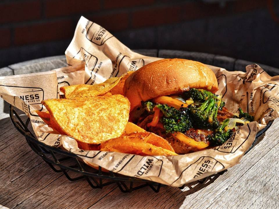 Hamburger from Arizona Wilderness Brewing Co with broccoli and bell peppers under the top bun and a side of potato chips