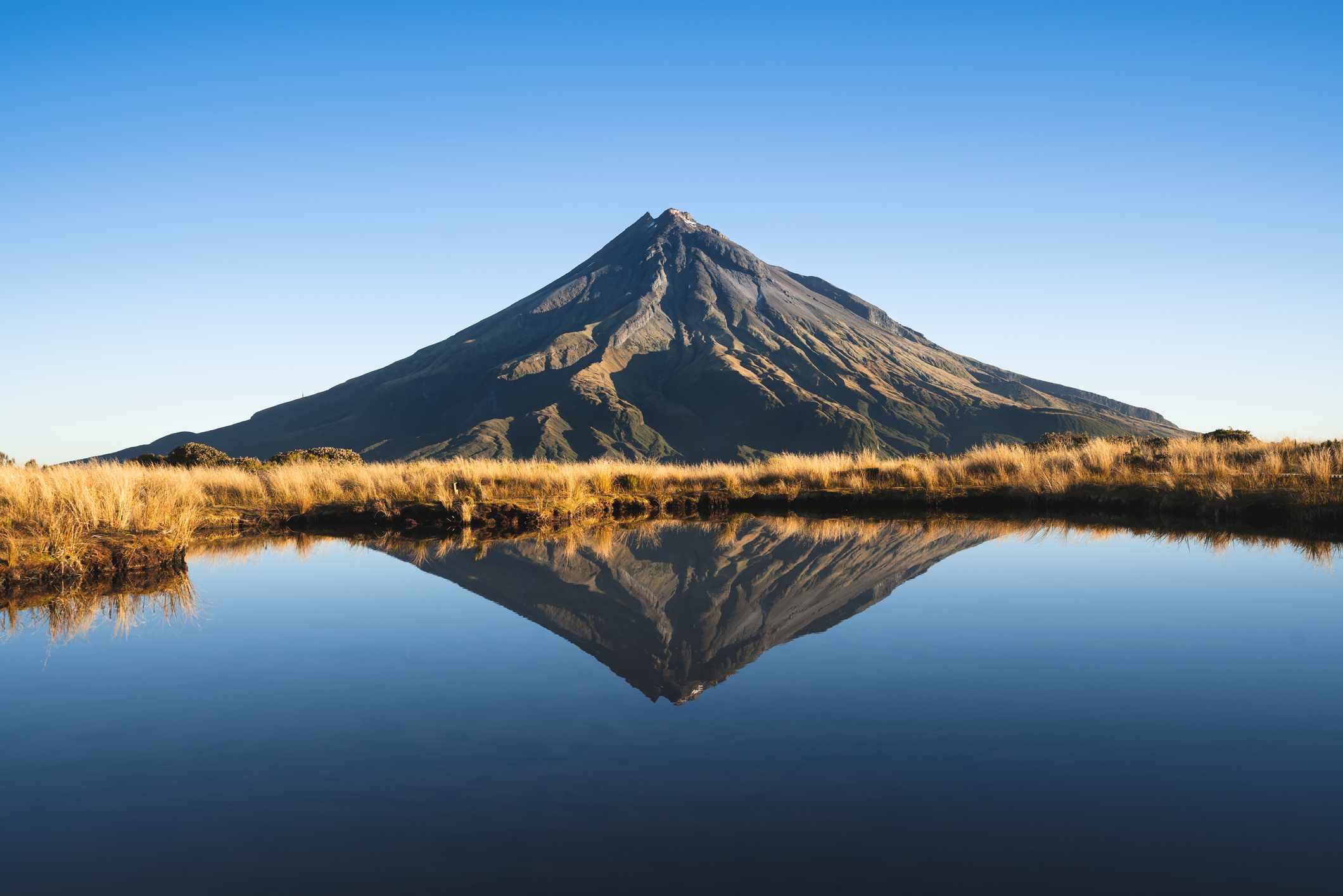 volcano with reflection in a lake and grassland in between