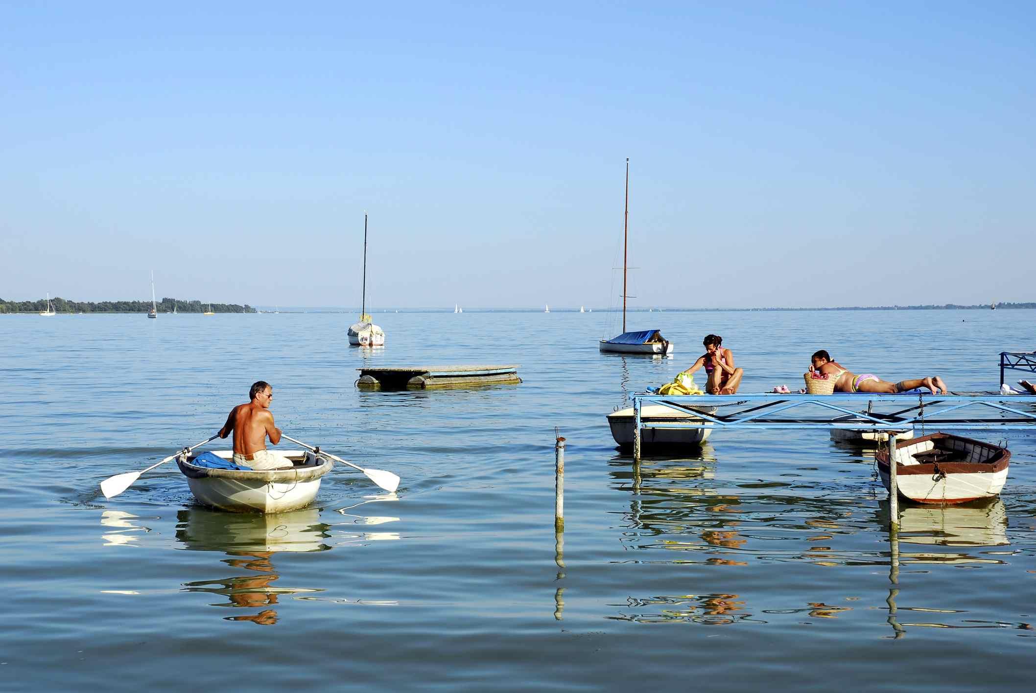 Women sunbathing on a jetty between boats, Keszthely, Lake Balaton, Hungary, Europe