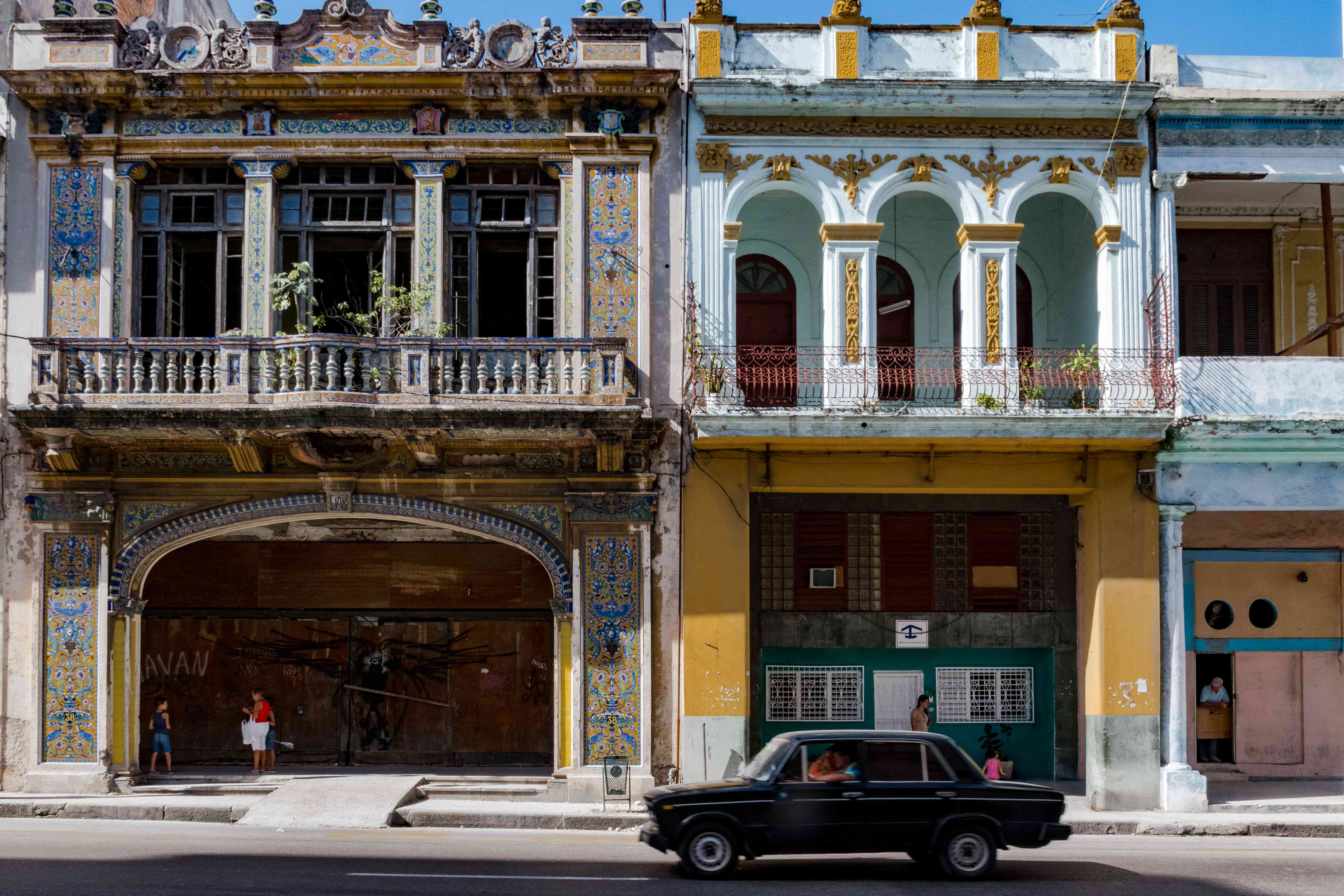 A classic car driving by ornate buildings in Old Havana