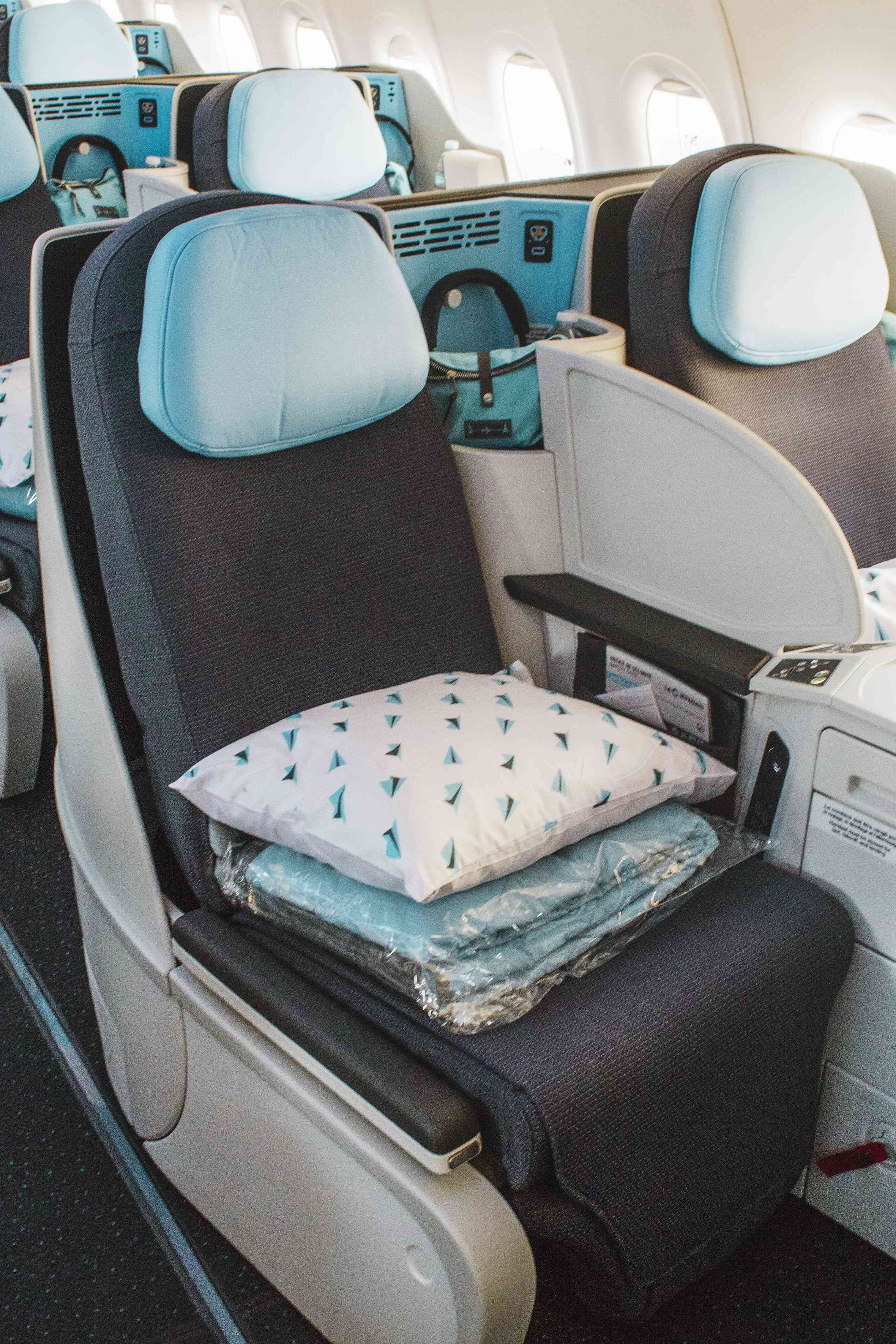 A shot of the full seat with the pillow and bedding with view of the headphones and amenity kit