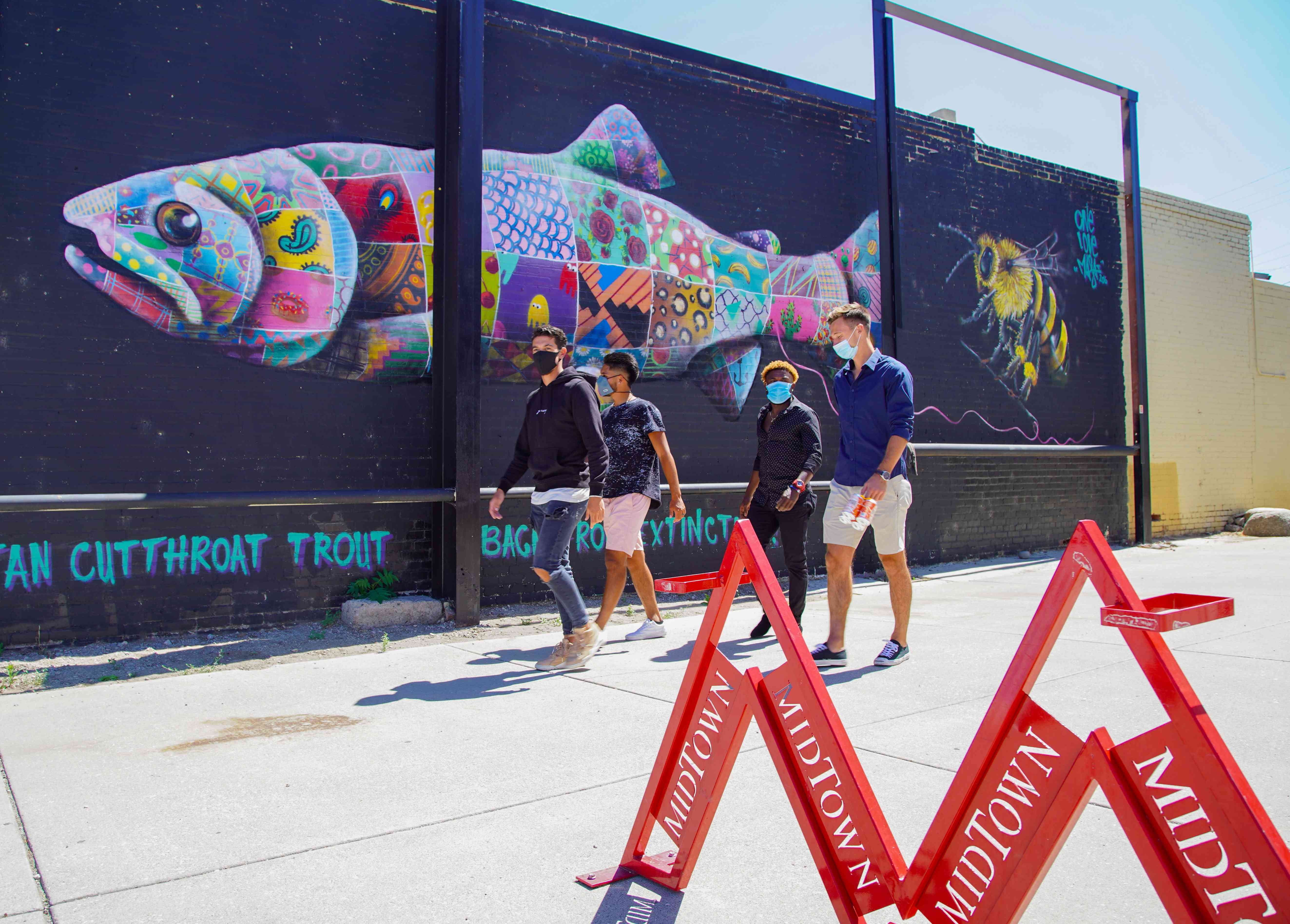 Diverse group of four men in masks walking in front of a mural of a fish in Midtown Reno