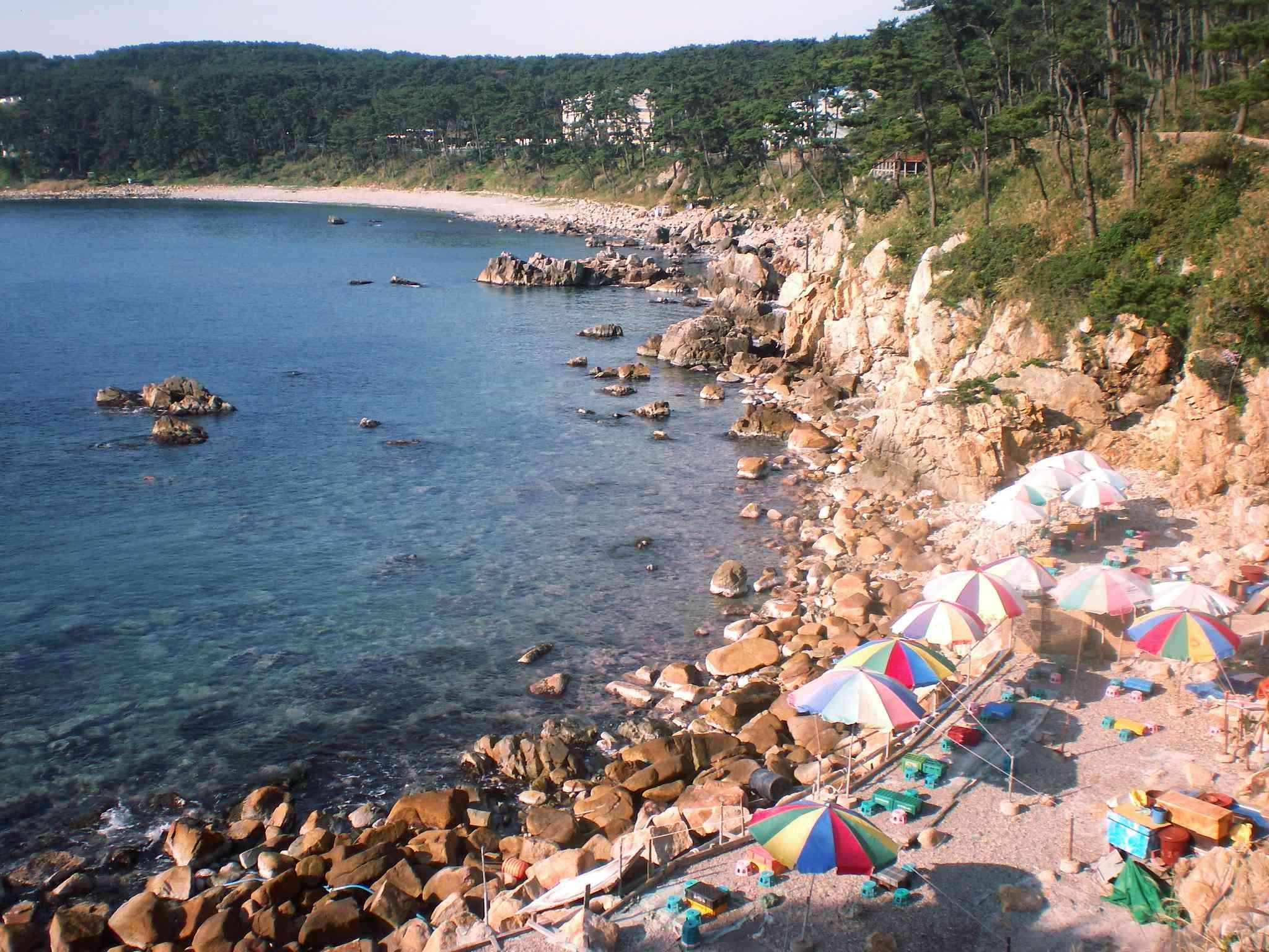 Beach umbrellas lined on the edge of Ilsan beach's rocky coastline