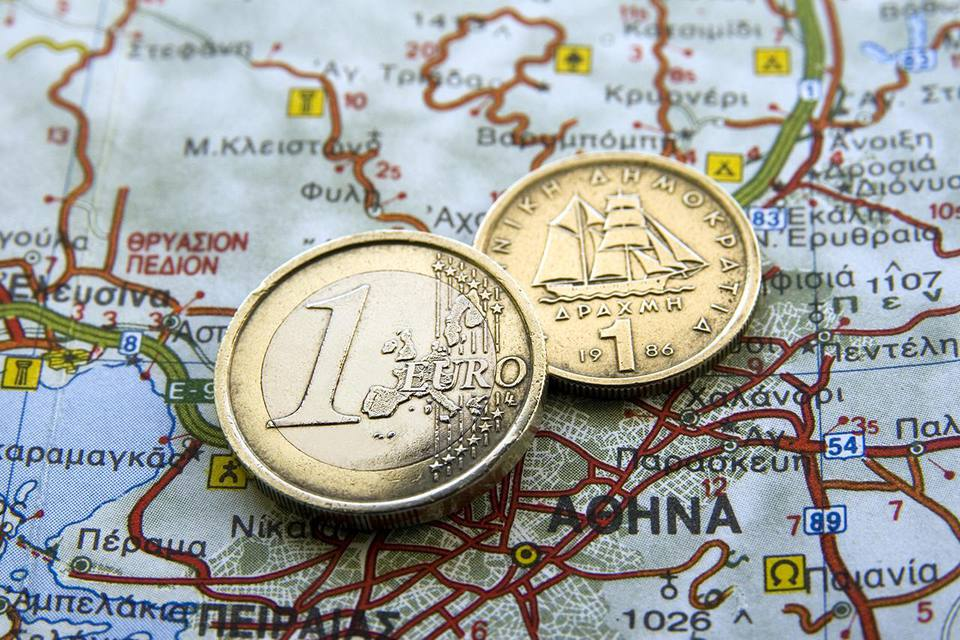 Euro coin and an old Greek coin drachma on a map