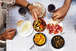 People eating tapas at outdoor restaurant, close-up of hands, overhead view.