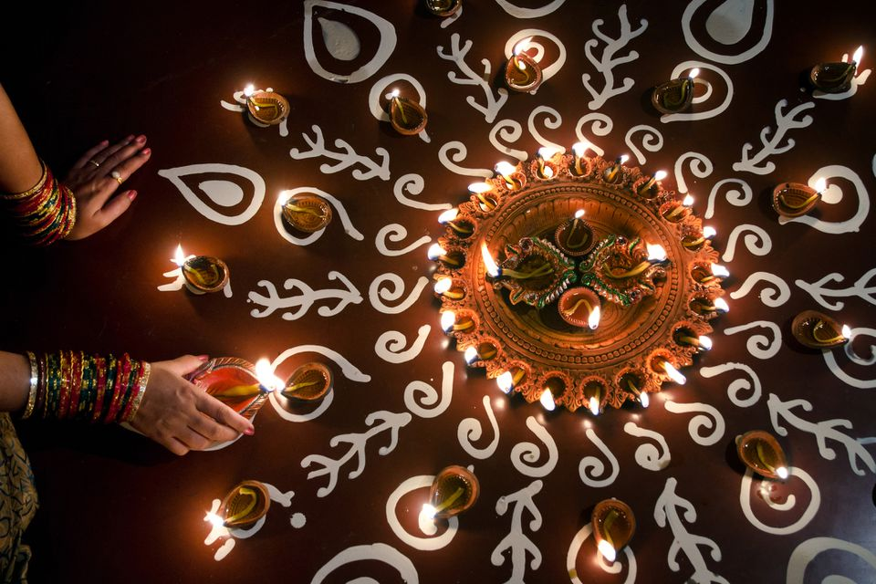 Lighting Diwali diyas.