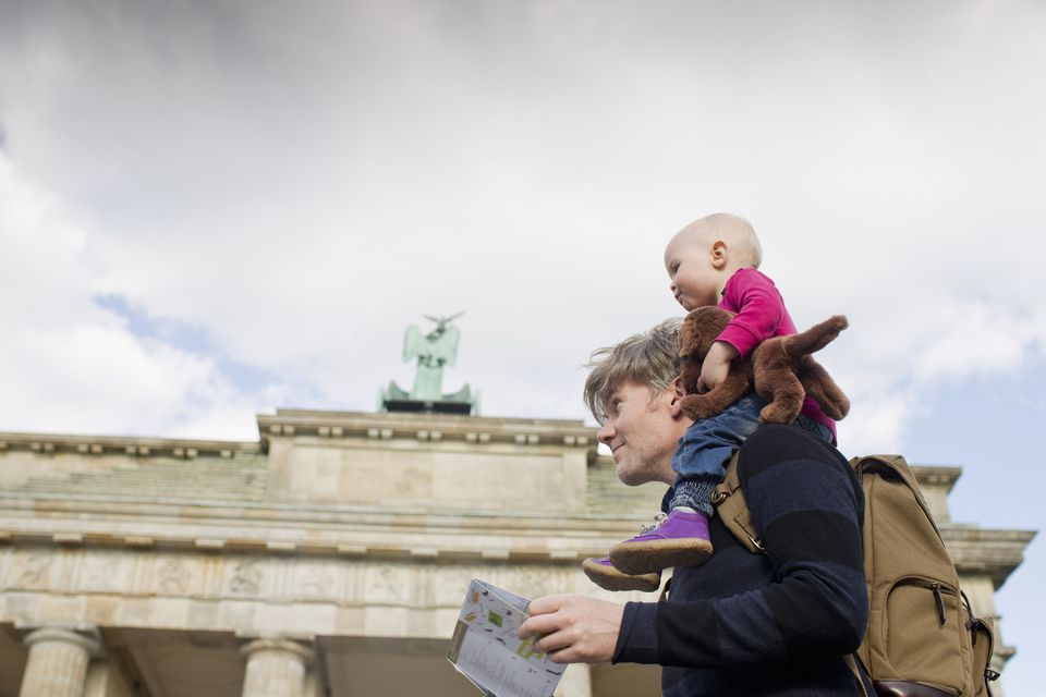 Father sightseeing whilst giving baby daughter shoulder ride, Brandenburg Gate, Berlin, Germany