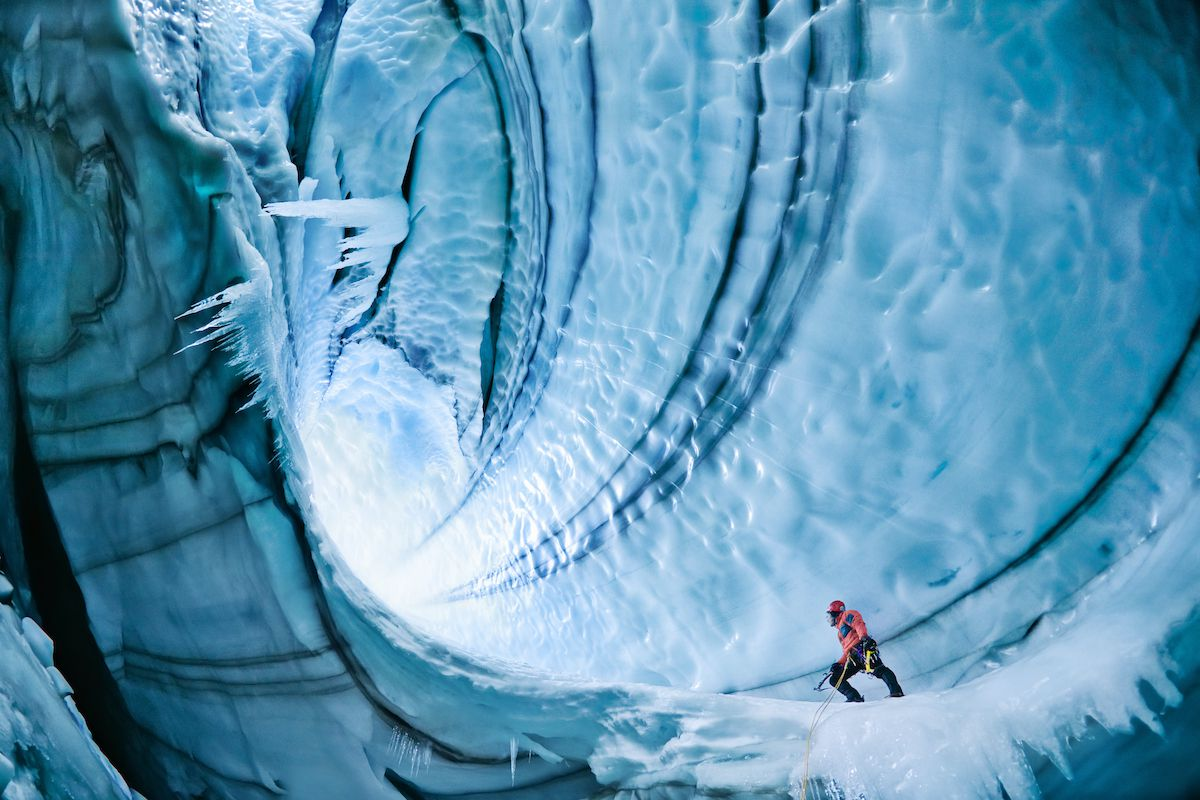 A climber makes his way up an ice cave